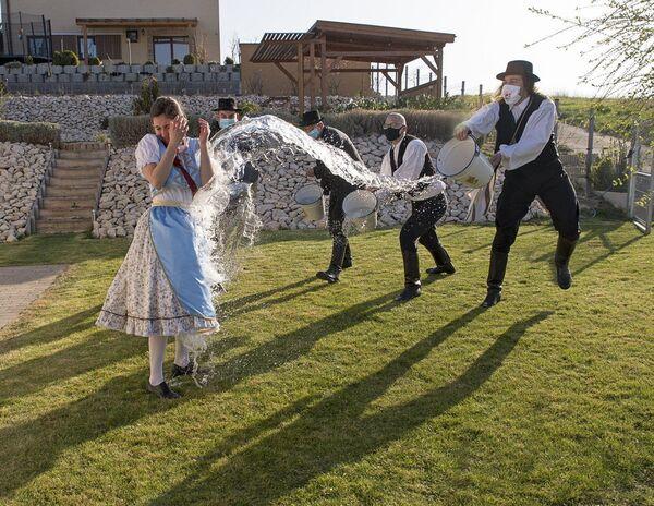 Podle staré maďarské tradice na Velikonoční pondělí mladí muži polévají vodou mladé ženy, Menfocsanak, Maďarsko.  - Sputnik Česká republika