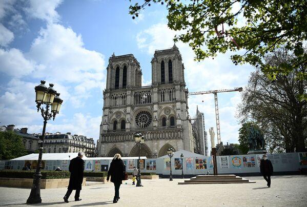 Kolemjdoucí na pozadí katedrály Notre Dame de Paris během její restaurace. - Sputnik Česká republika