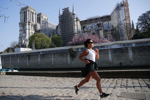 Běžící dívka na pozadí katedrály Notre Dame de Paris během její restaurace. - Sputnik Česká republika