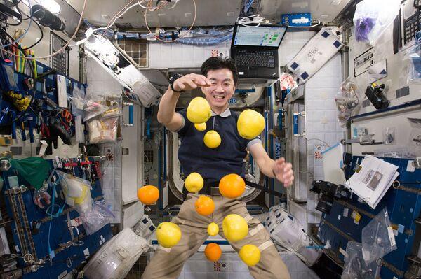 Astronaut Japonské agentury pro průzkum letectví a kosmonautiky (JAXA) Kimiya Yui nahání dodávku čerstvého ovoce, která dorazila na palubu.  - Sputnik Česká republika