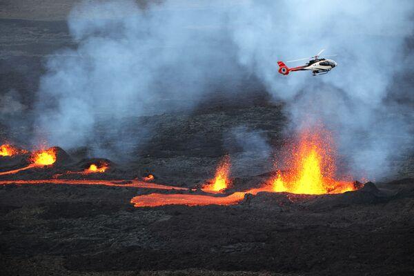 Vrtulník nad chrlící lávu sopkou Piton de la Fourno na ostrově Réunion.  - Sputnik Česká republika
