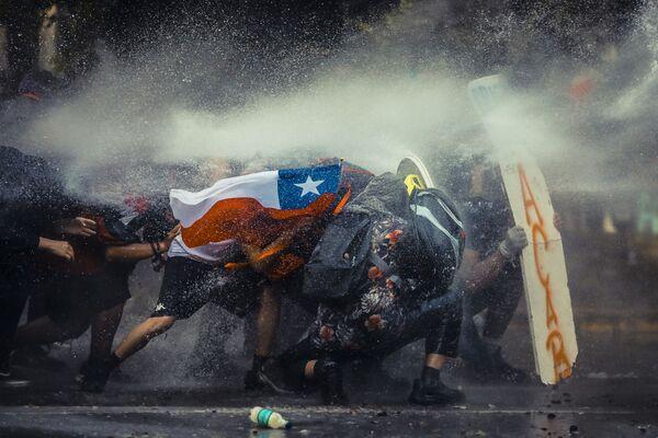 Demonstranti se chrání štítem před vodními děly používanými speciálními policejními jednotkami během protestů v Chile. - Sputnik Česká republika