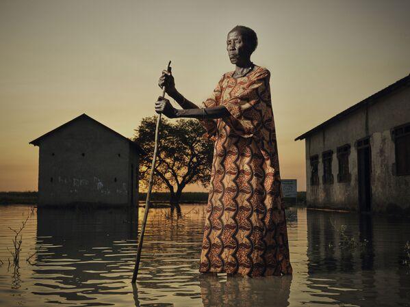 Žena se pohybuje po zatopené vesnici v jižním Súdánu. - Sputnik Česká republika