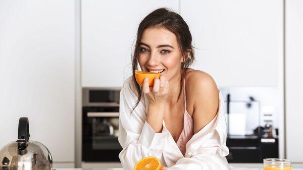 Девушка ест апельсин на кухне - Sputnik Česká republika