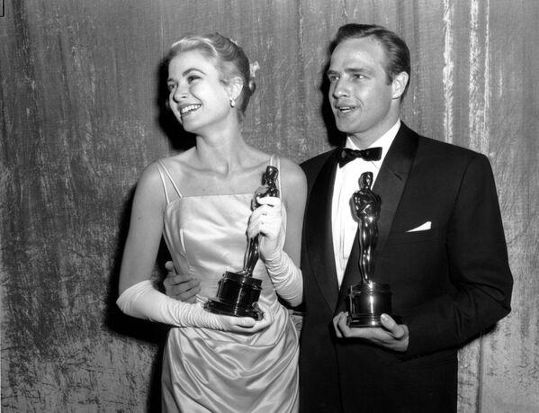 Držitelé Oscara Grace Kellyová a Marlon Brando v roce 1955 v hollywoodském divadle RKO Pantages. Kellyová se stala nejlepší herečkou roku za roli ve filmu Děvče z venkova. Brando se stal nejlepším hercem roku za roli ve filmu V přístavu - Sputnik Česká republika