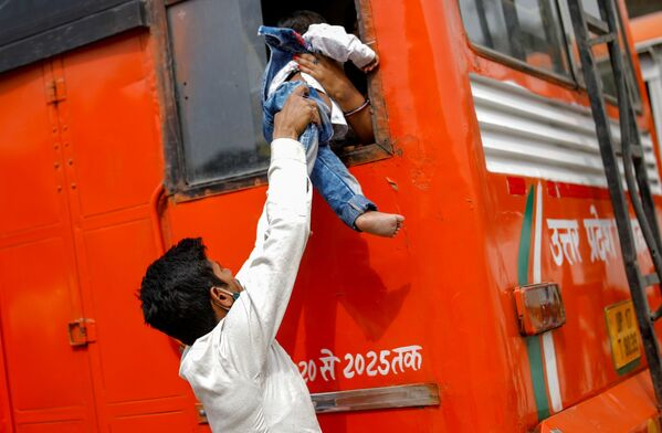 Migrant předává svého syna do okna autobusu v Indii - Sputnik Česká republika