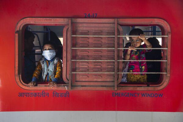 Chlapci se dívají z okna vlaku na vlakovém nádraží v Indickém Gauhati - Sputnik Česká republika