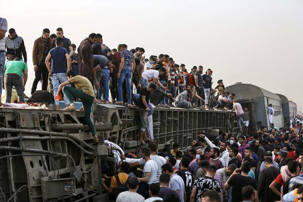 Lidé po srážce vlaků ve městě Tuh v Egyptě lezou na převrácený vagón - Sputnik Česká republika
