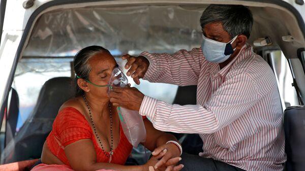 Муж поправляет кислородную маску своей жены, пока они ждут в машине, чтобы попасть в больницу с COVID-19 для лечения, Индия - Sputnik Česká republika