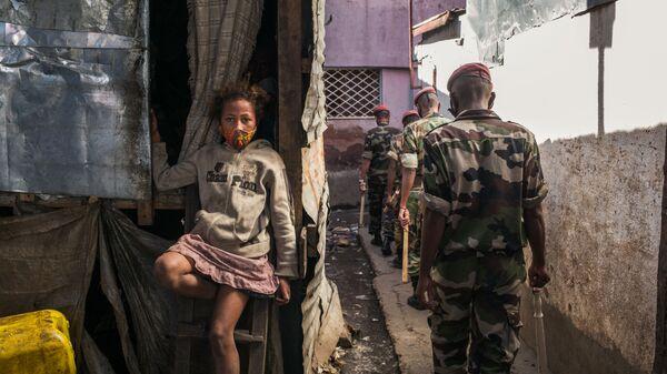 Ребенок с защитной маской на улице в Антананариву, патрулируемой военнослужащими - Sputnik Česká republika