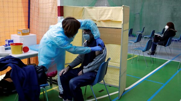 Медицинский работник делает мужчине прививку от коронавируса в центре массовой вакцинации в одном из спортзалов Праги, Чехия - Sputnik Česká republika
