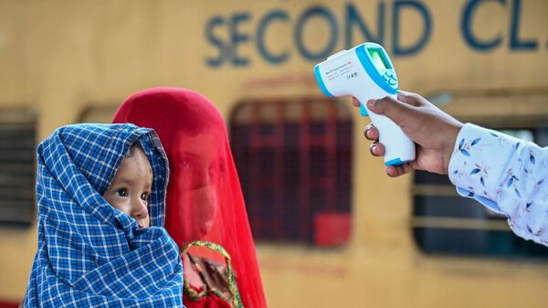 Медицинский работник проверяет температуру тела ребенка во время скрининга на коронавирус Covid-19 в Мумбаи - Sputnik Česká republika