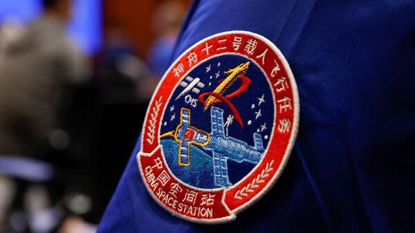 Нашивка с изображением космического полета Шэньчжоу-12 на штатном сотруднике в Китае  - Sputnik Česká republika