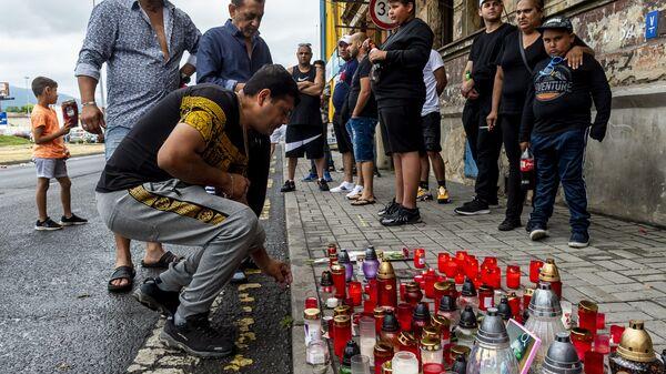 Мужчина зажигает свечу на месте смерти цыгана в Теплице - Sputnik Česká republika