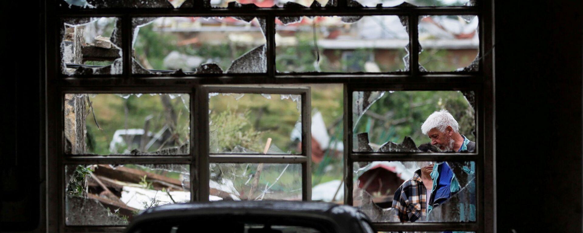 Lidé stojí u rozbitého okna po tornádu, které zasáhlo vesnici Mikulčice - Sputnik Česká republika, 1920, 26.06.2021