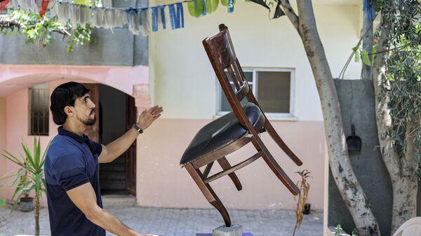 Палестинец во время балансировки стула на кирпиче в городе Бейт-Лахия - Sputnik Česká republika