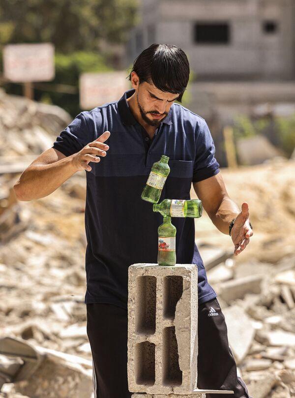 Tady zase umělec ukládá láhve na kusy cihel. - Sputnik Česká republika