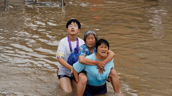 Женщина несет пожилую женщину  через паводковые воды после проливного дождя в Чжэнчжоу, провинция Хэнань, Китай - Sputnik Česká republika