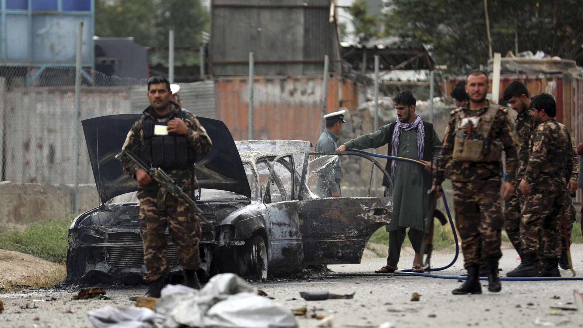 Сотрудники службы безопасности осматривают поврежденный автомобиль, поврежденный во время обстрела Кабула - Sputnik Česká republika, 1920, 18.08.2021