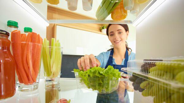 Девушка перед открытым холодильником с овощами и фруктами - Sputnik Česká republika
