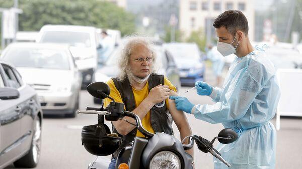Медицинский работник применяет дозу вакцины против коронавируса в центре вакцинации для автомобилей в Берлине - Sputnik Česká republika