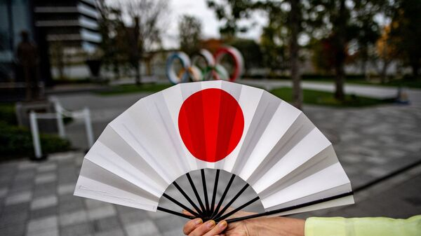 Веер с японским флагом напротив Олимпийских колец в Токио  - Sputnik Česká republika
