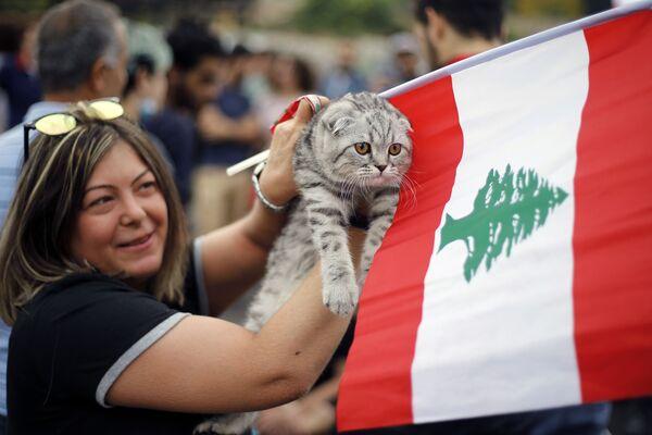 Demonstrantka drží svou kočku a libanonskou vlajku během protestu v libanonském Bejrútu - Sputnik Česká republika