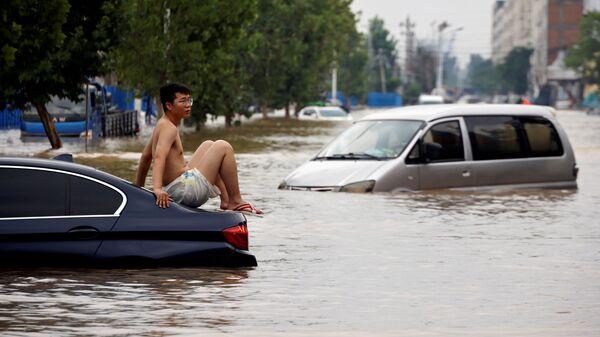 Мужчина сидит на застрявшем автомобиле на затопленной дороге после проливного дождя в Чжэнчжоу, провинция Хэнань, Китай - Sputnik Česká republika