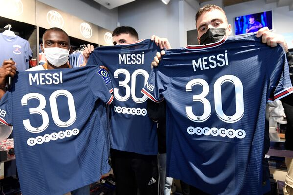 Fanoušci fotbalového klubu PSG drží dresy se jménem Lionela Messiho. - Sputnik Česká republika