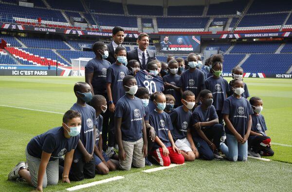 Lionel Messi a prezident PSG Nasser Al-Khelaifi se fotí s dětmi na stadionu Parc des Princes. - Sputnik Česká republika