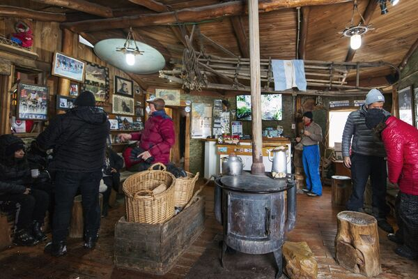 Turisté si pochutnávají na horké čokoládě po jízdě se psím spřežení na chatě v komplexu Siberianos de Fuego. - Sputnik Česká republika
