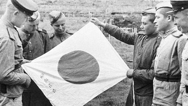 Советские воины рассматривают брошенный при отступлении японский флаг - Sputnik Česká republika