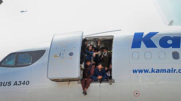 Афганцы сидят в дверях самолета в аэропорту Кабула  - Sputnik Česká republika