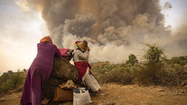 Женщины с вещами на дороге во время лесных пожаров в районе Шефшауэн на севере Марокко - Sputnik Česká republika