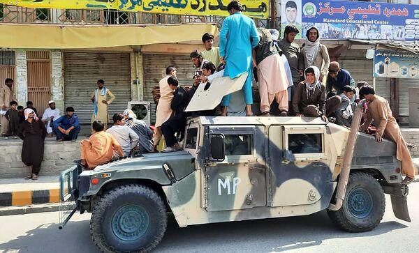 Bojovníci Tálibánu (teroristická organizace zakázaná v Rusku a několika dalších zemích) a místní obyvatelé sedící ve vojenském vozidle afghánské národní armády v provincii Laghmán - Sputnik Česká republika