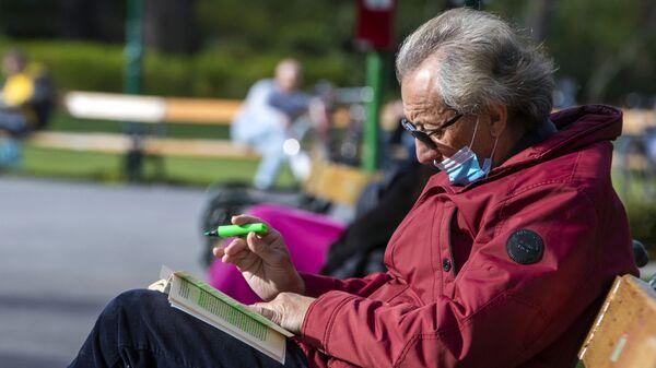 Пожилой мужчина в медицинской маске во время отдыха в одном из парков в Вене - Sputnik Česká republika