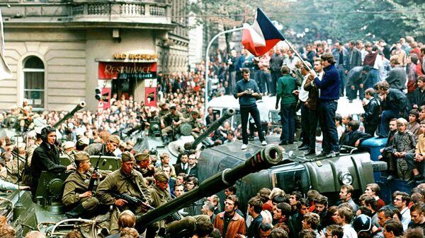 Чешская молодежь с чехословацкими флагами стоит на перевернутом грузовике, пока другие жители Праги окружают советские танки в центре Праги 21 августа 1968 года - Sputnik Česká republika