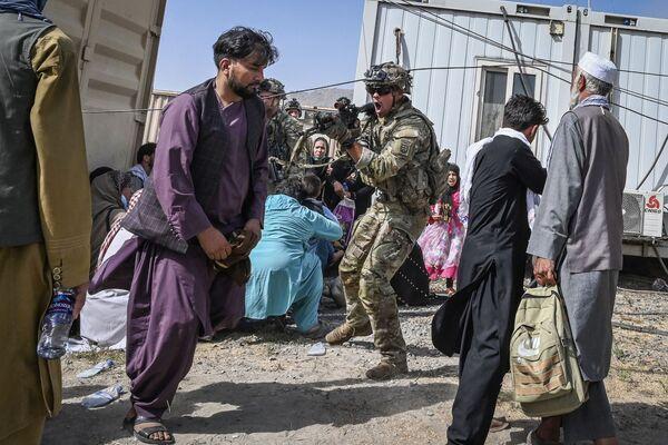 Americký voják míří na Afghánce na kábulském letišti - Sputnik Česká republika