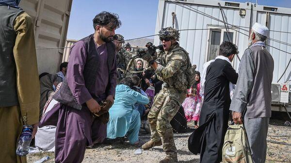 Американский солдат целится в афганцев в аэропорту Кабула  - Sputnik Česká republika