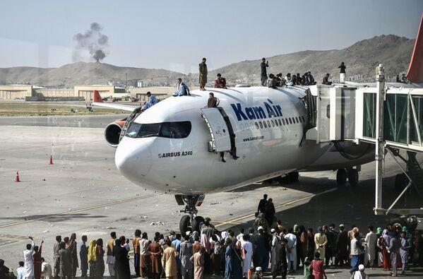 Afghánci nastupují do letadla na letišti po vstupu Tálibánu (teroristická organizace zakázaná v Rusku) do Kábulu - Sputnik Česká republika