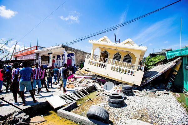 Lidé stojí poblíž domu zničeného zemětřesením o síle 7,2 stupně v Les Cayes na Haiti - Sputnik Česká republika