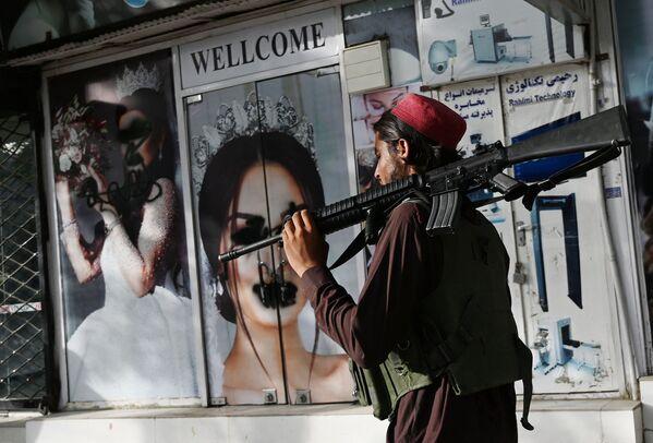Militant Tálibánu (teroristická organizace zakázaná v Rusku) jde kolem salonu s obrázky žen potřísněných sprejem v Kábulu - Sputnik Česká republika