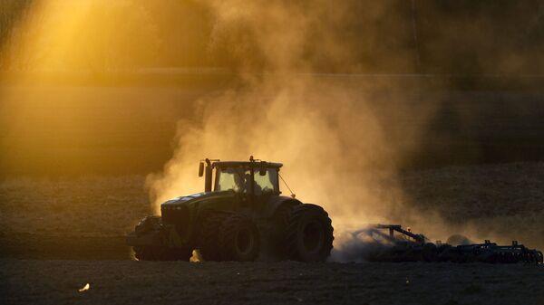 Трактор в поле на фоне заката в Минске, Белоруссия - Sputnik Česká republika