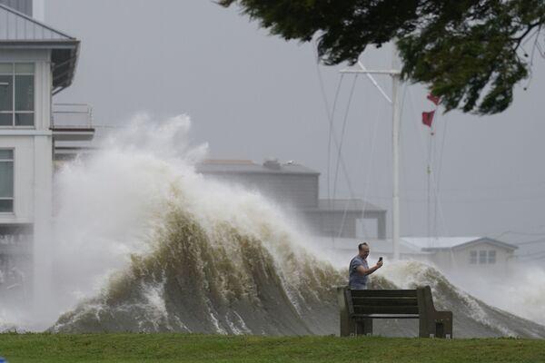 Muž fotografuje vysoké vlny na břehu jezera Pontchartrain, když se k New Orleans blíží hurikán Ida - Sputnik Česká republika