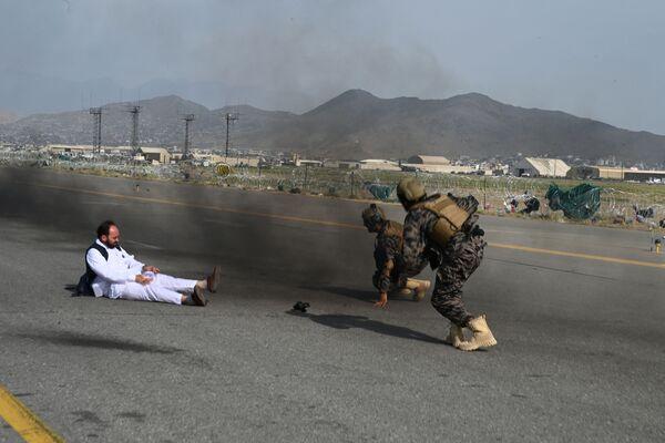 Bojovníci speciálních sil Tálibán Badrí* a novinář, jak vstávají po pádu z auta na letišti v Kábulu - Sputnik Česká republika