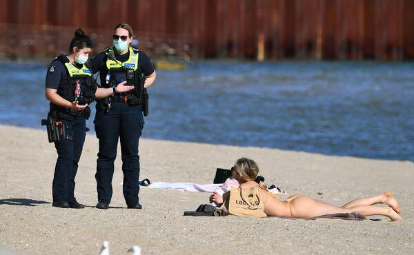 Policie mluví s ženou, která se opalovala na pláži St. Kilda v Melbourne během samoizolačního režimu - Sputnik Česká republika