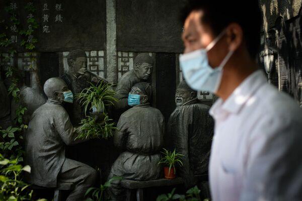 Muž prochází kolem soch v rouškách u restaurace v Pekingu, Čína - Sputnik Česká republika