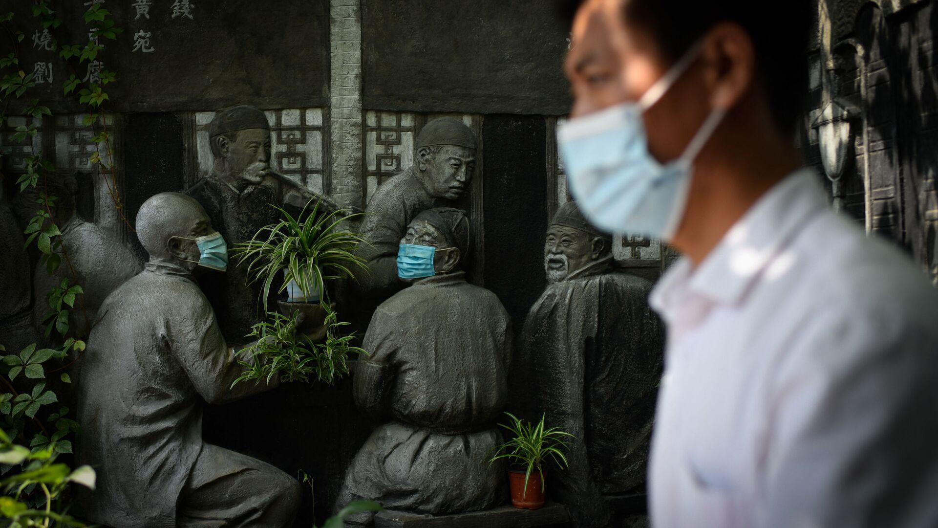 Muž prochází kolem soch v rouškách u restaurace v Pekingu, Čína - Sputnik Česká republika, 1920, 12.09.2021