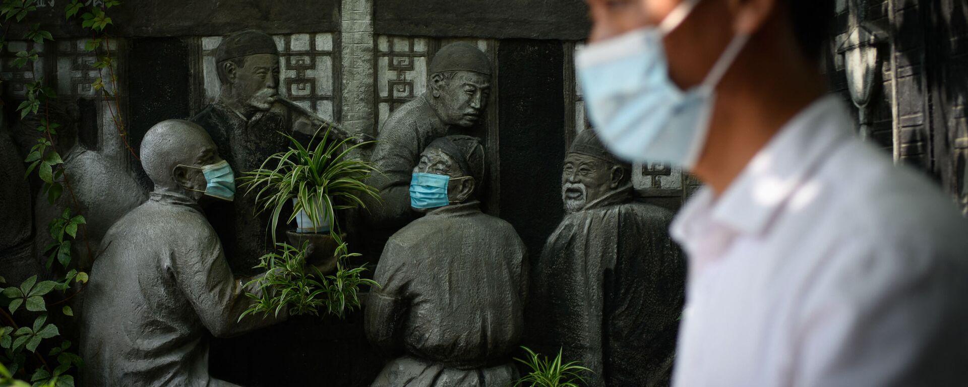 Muž prochází kolem soch v rouškách u restaurace v Pekingu, Čína - Sputnik Česká republika, 1920, 27.09.2021