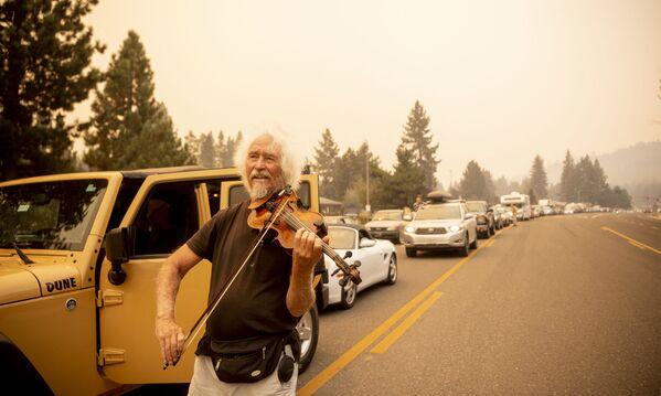 Mel Smothers hraje na housle v dopravní zácpě s evakuovanými na silnici v Kalifornii, USA - Sputnik Česká republika